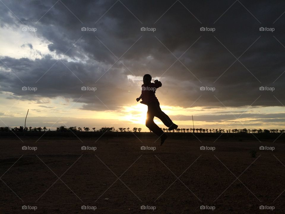 Silhouette of a man jumping during sunset