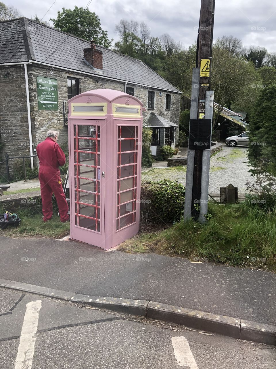 "I captured this man repainting a derelict British phone box. He had not finished so perhaps here is the UK's only ""pink telephone box."""