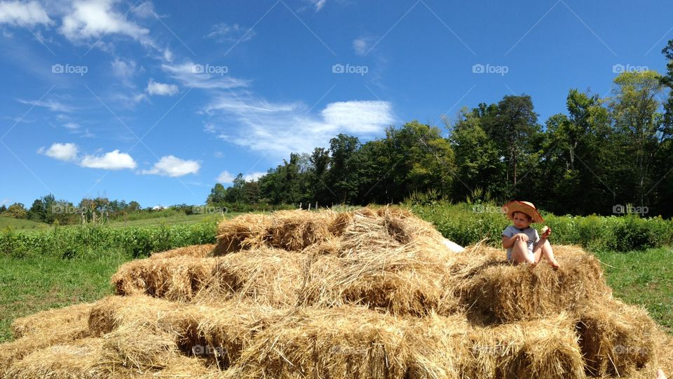 Kid sitting on a haystack in the sun. Panoramic.