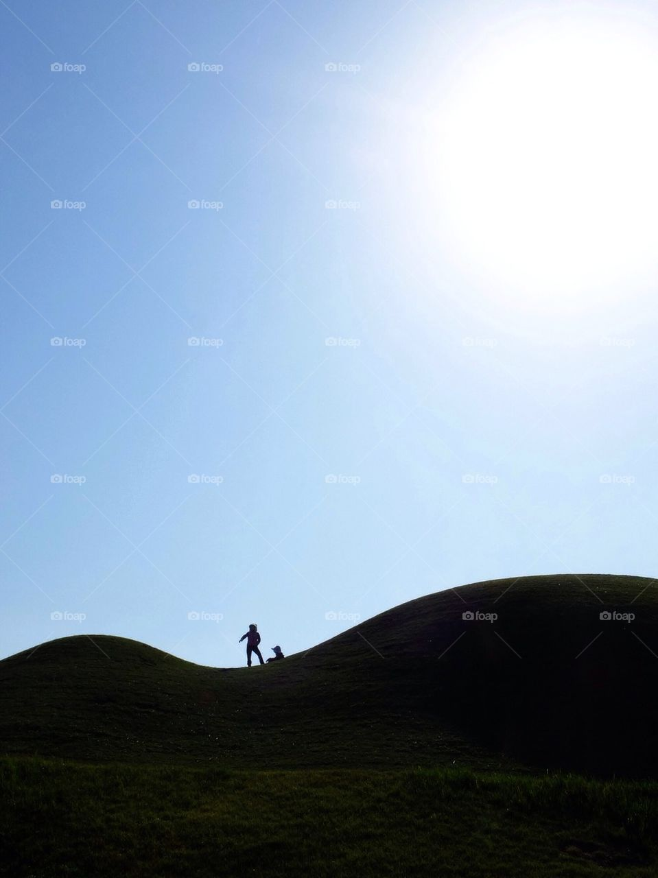 Silhouette of 2 persons on a rolling hill
