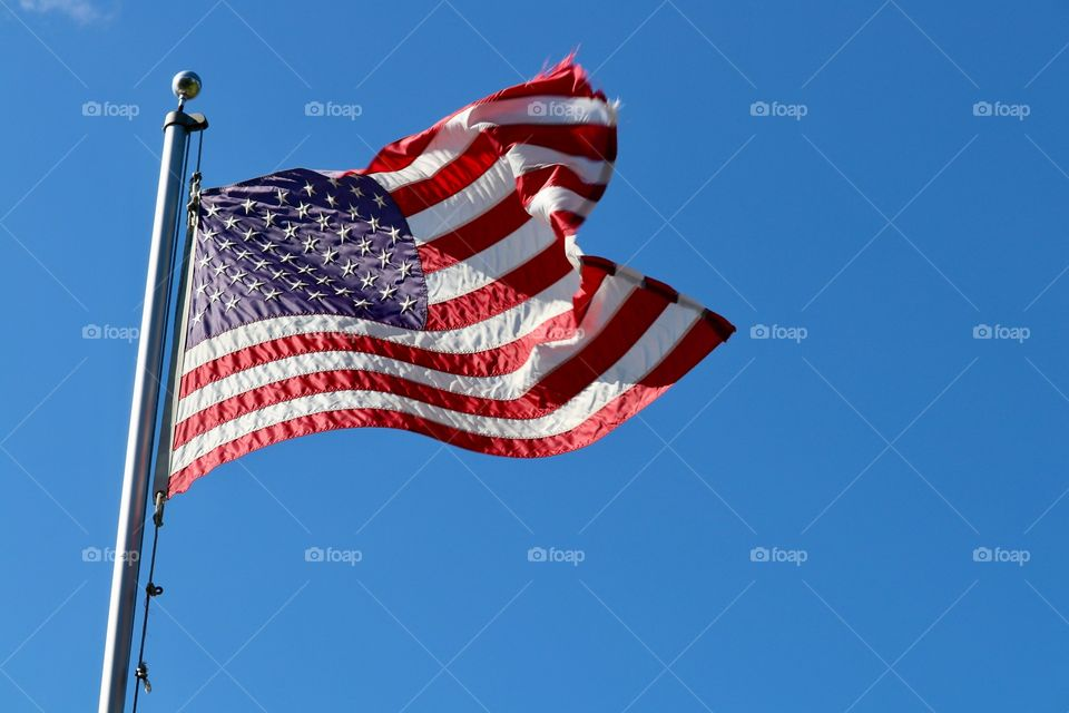 American flag high on flagpole blowing in the breeze against a colourful vivid blue clear sky