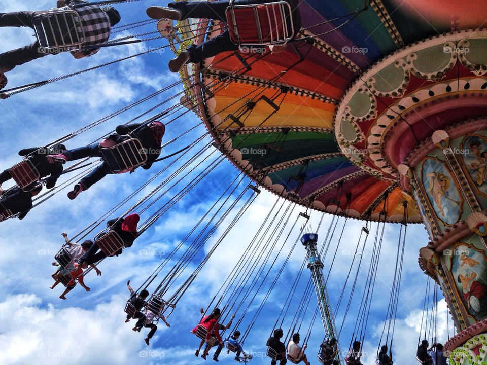 Low angle view of people on swing in carousel