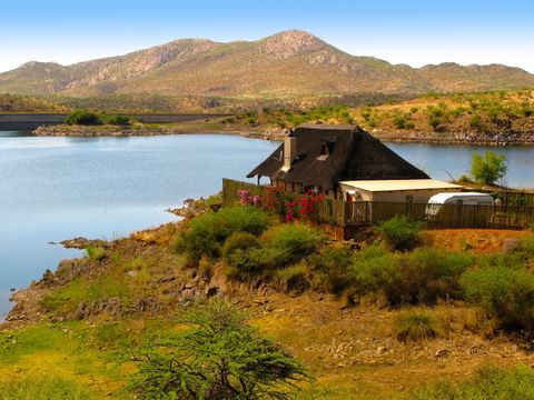 Lake Oanob view with mountains, house and acacia trees in Central Namibia