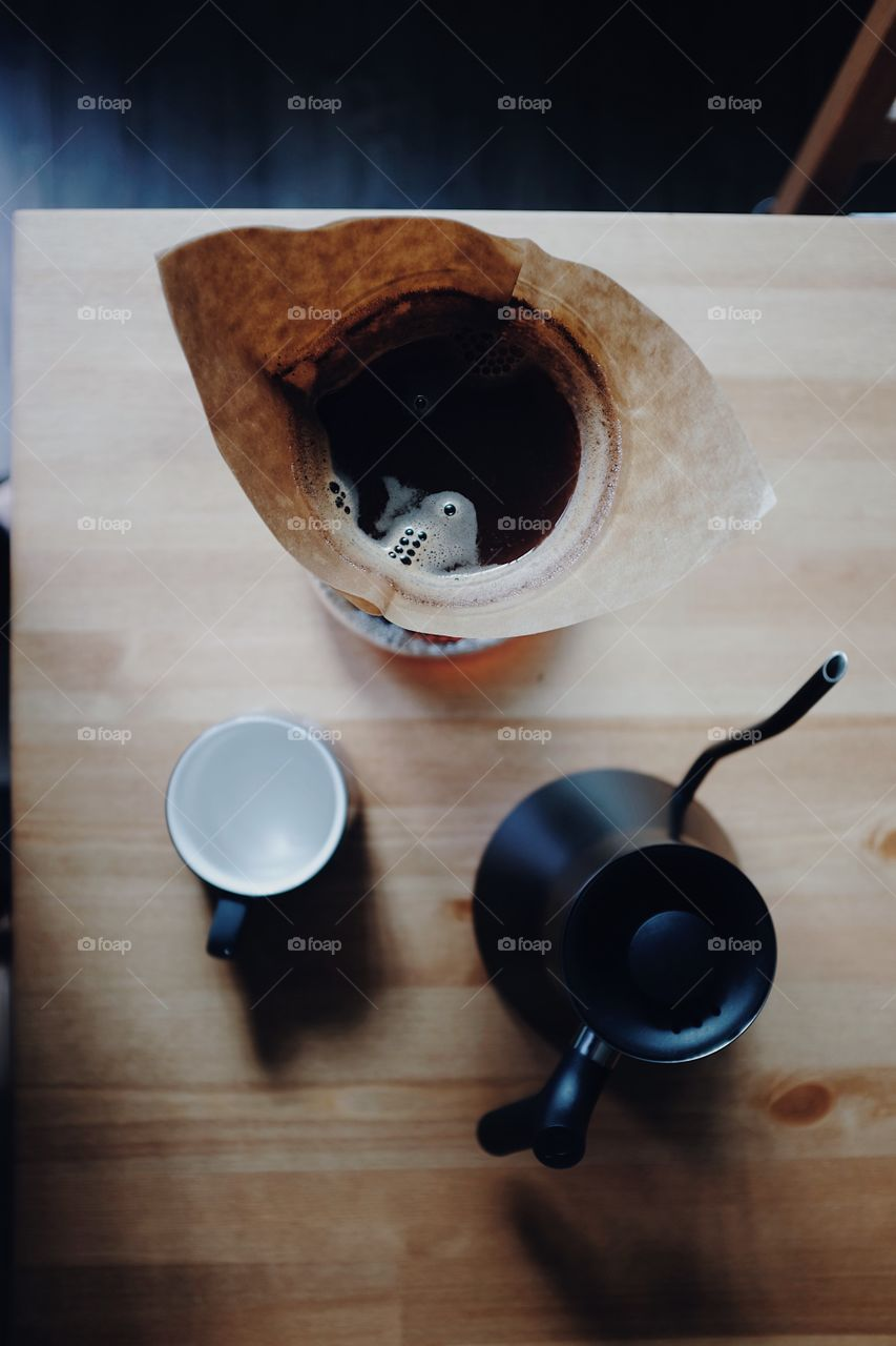 Chemex coffee about to be served into a ceramic mug on a table with some soft light.
