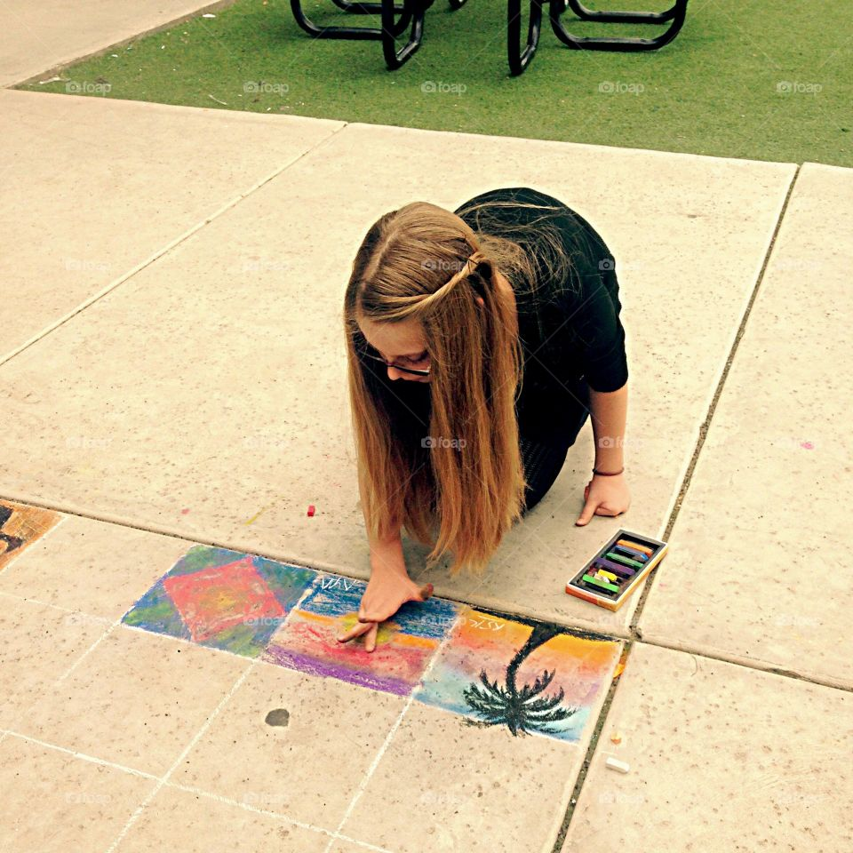 Teenager at the school painting on ground