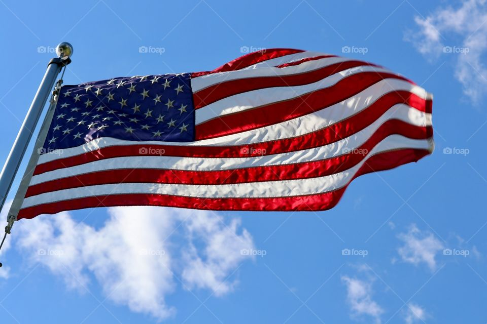 American red white and blue Stars and Stripes flag on flagpole flapping in the wind against a bright vivid blue clear sky suitable for background image