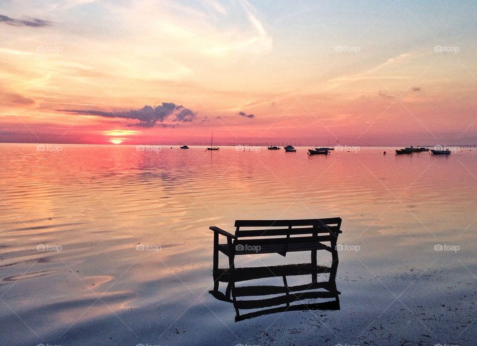 Bench in the water during sunset