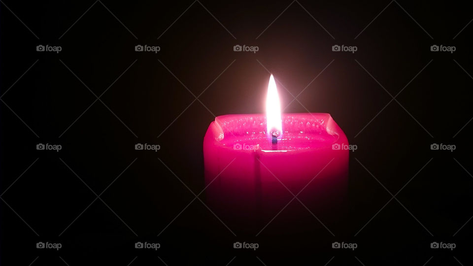 Close-up of illuminated red candle