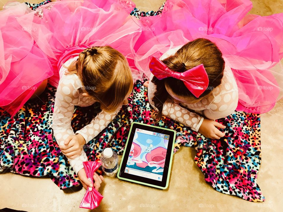 Two darling girls in pink dance costumes watching their iPad before going out to dance!