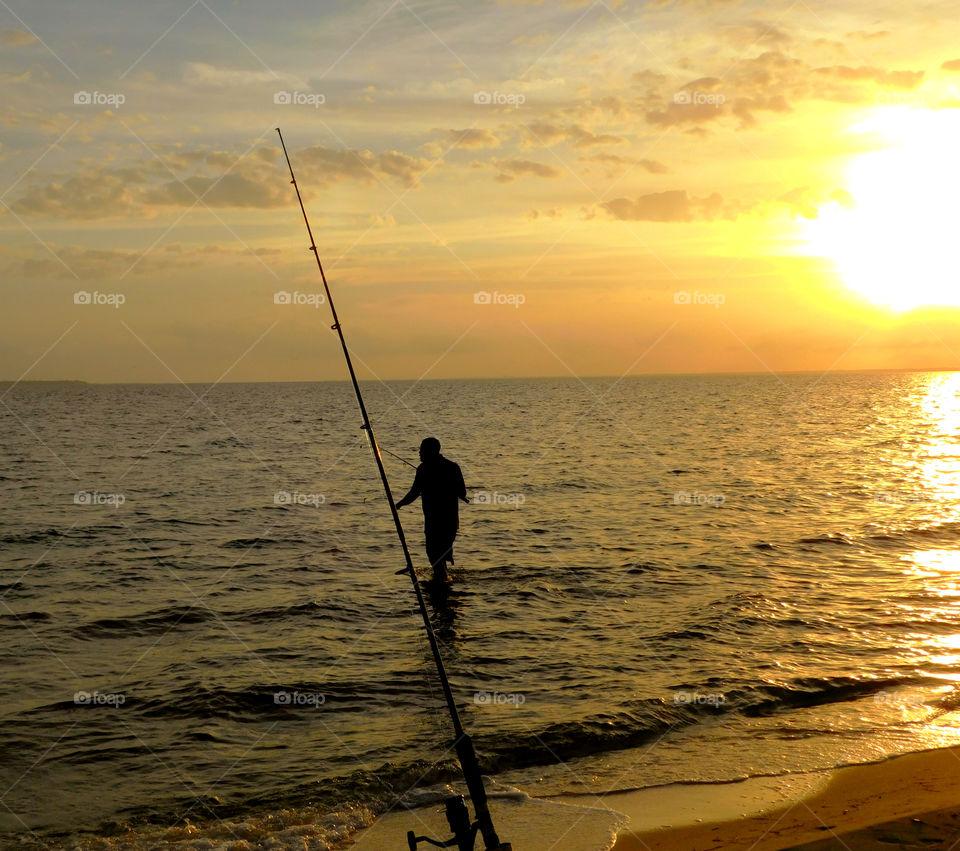Fisherman fishing in sea
