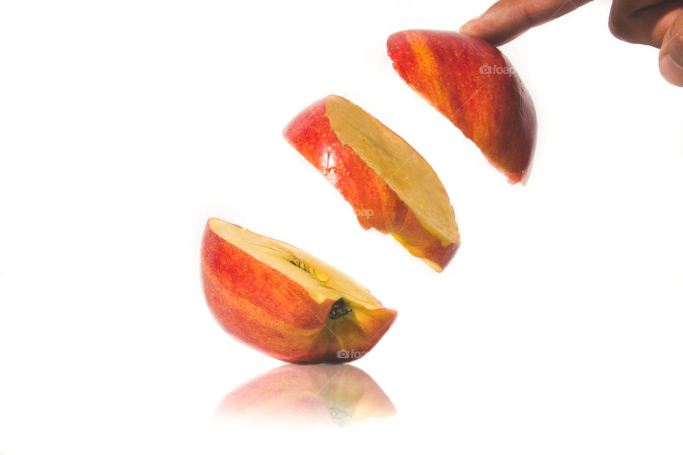 Hand with apple slice on white background