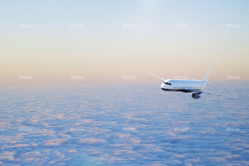Aero plane flying above cloud at sunset