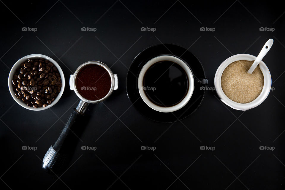 Composition using symmetrical shapes and lines. Coffee scene with beans porta filter cup and sugar. Simple with negative space around image. Flat lay from top.