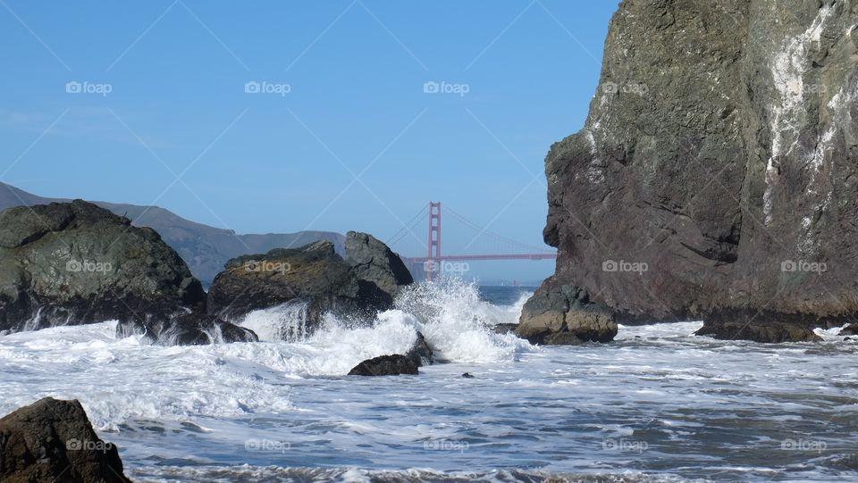 Mile rock beach SF. Playful waves crash and spray tiny delights of droplets on this beach. Golden Gate visible.