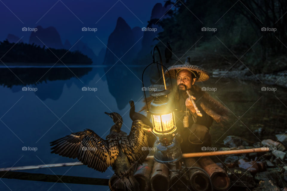 Cormorant fisherman and his birds with lantern on the river