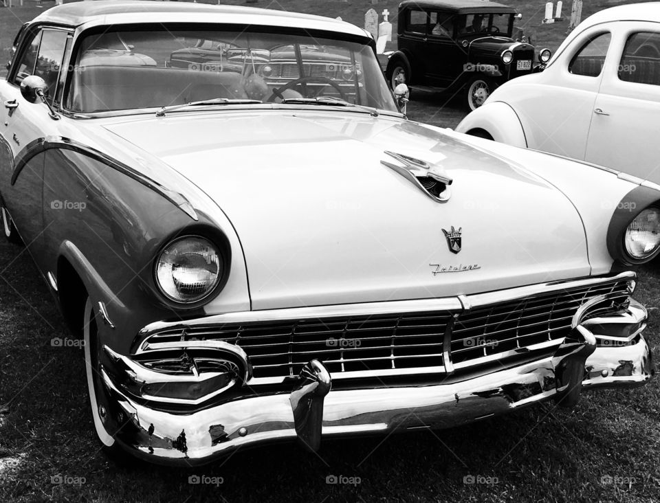 Black and white image of classic antique cars. Ford Fairlane , model t in background.