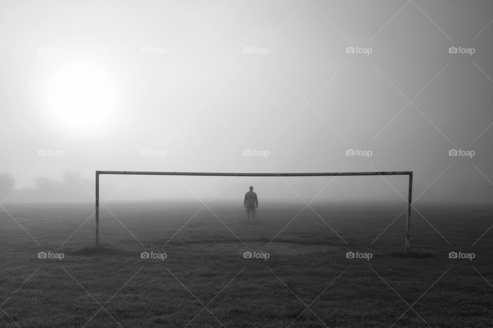A lone footballer standing in the goal on a cold and foggy morning with no other players in sight.