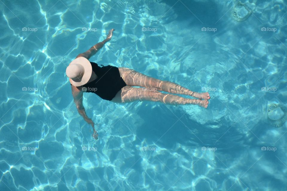 A lady enjoys a refreshing dip in the swimming pool.