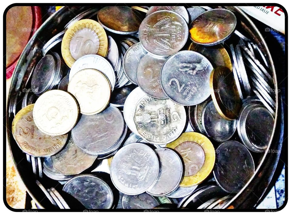 In this photo there is bunch of coins in a bowl.Its shows the currency of india and the coins of ₹1,₹2,₹5 and _10 rupees coins..