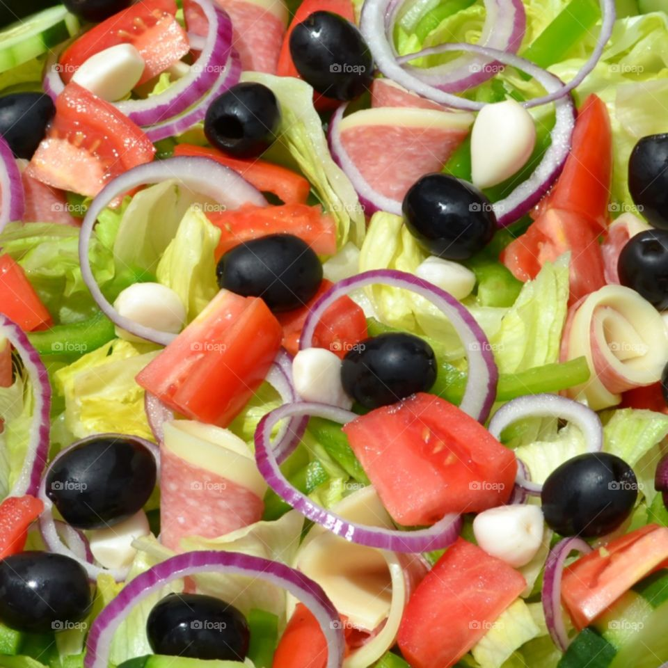 Antipasto salad of lettuce, tomatoes, black olives, red onions rings, garlic, salami, provolone and mozzarella cheese, and green peppers