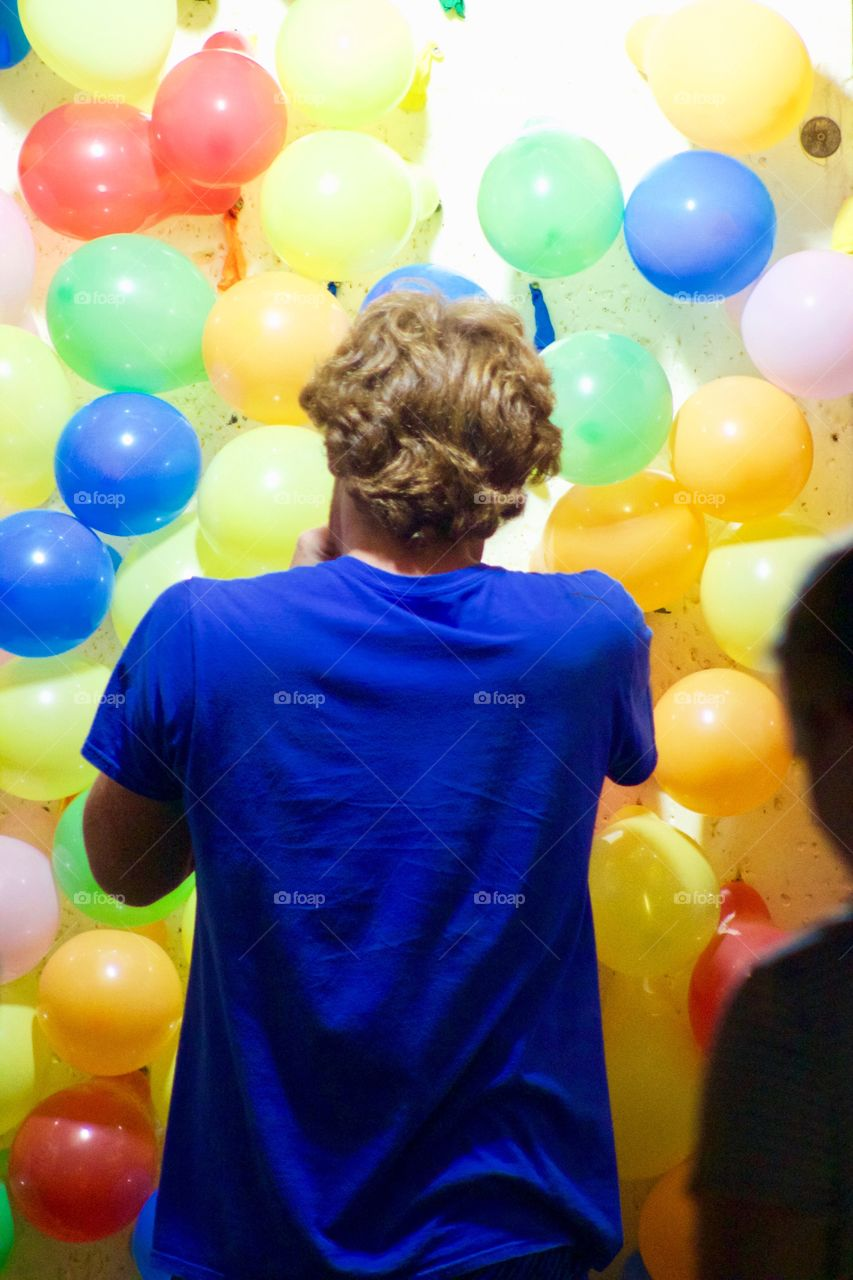 A young man in a royal blue t-shirt blows up brightly colored balloons in a carnival game booth