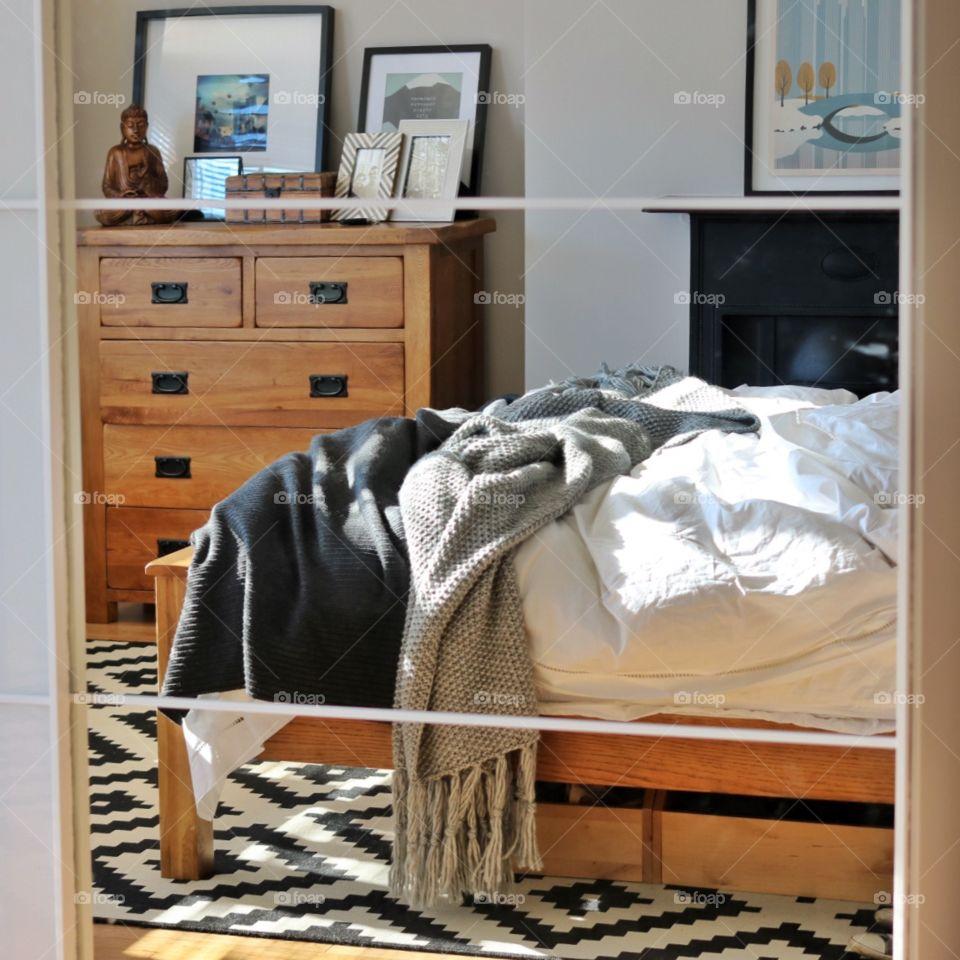 Unmade bed in reflection. Grey bedroom with wooden floor.