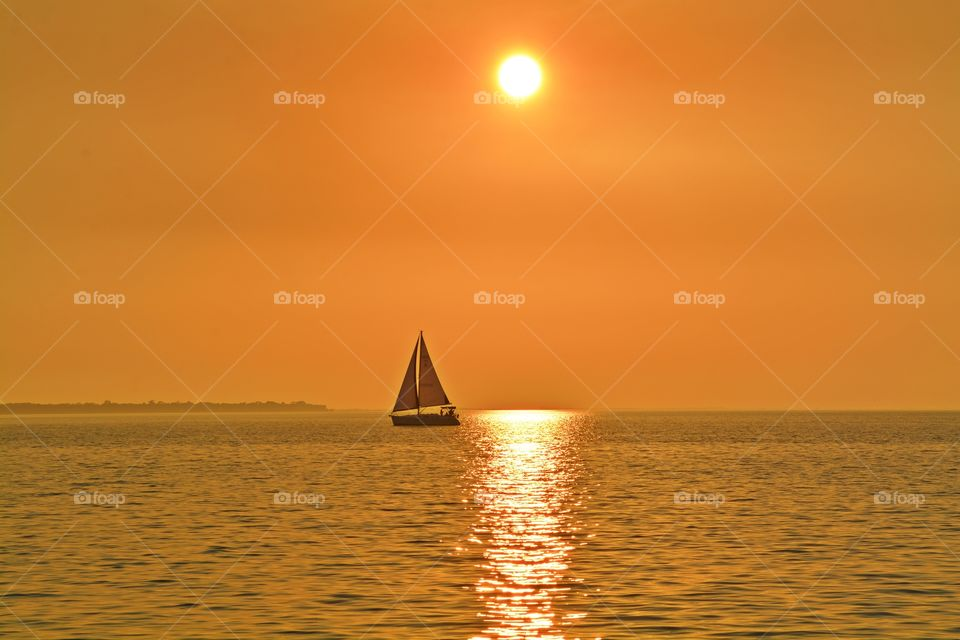 Sunrise, sunset and the moon - Destination unknown - Sailing in the magnificent golden sunset over the glistening bay water