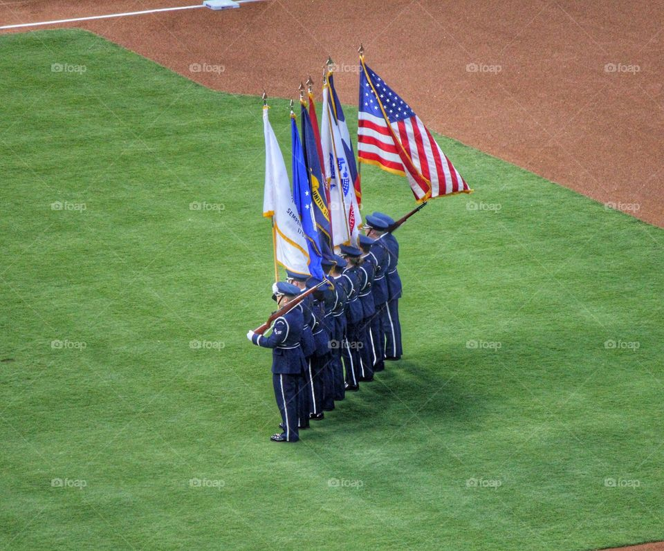 Stand with pride. Military holding flags at a baseball game in Arlington Texas