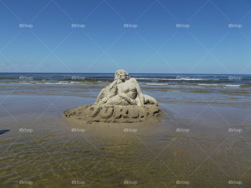 Mermaid sculpture out of the send on the beach un Jūrmala, Latvija