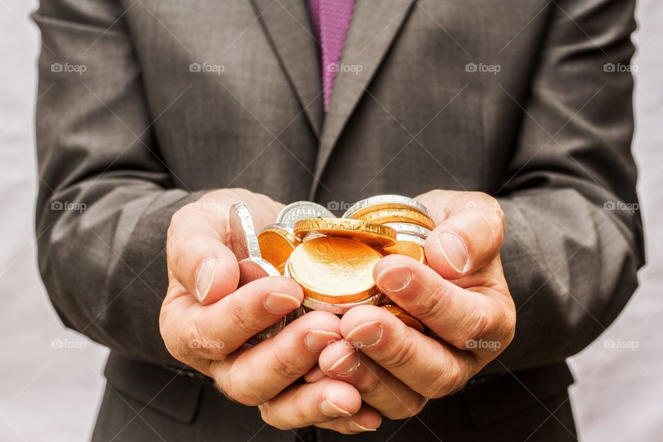 A close up of a man's cupped hands holding lots of gold and silver chocolate coins.