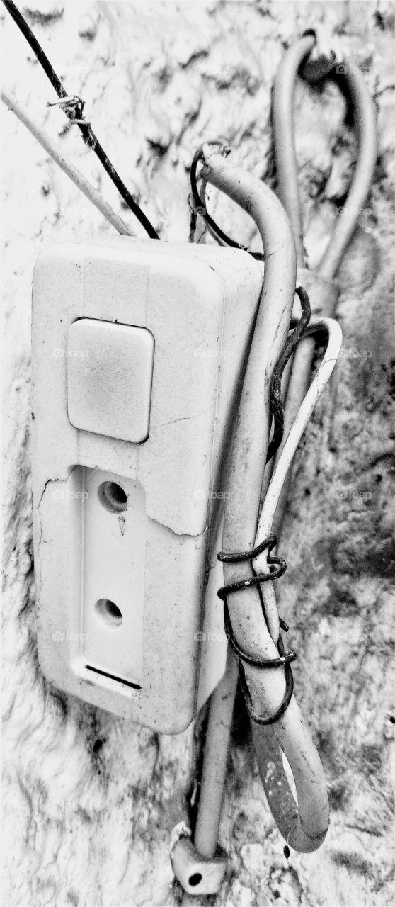 Alte defekte Klingel mit losen Kabeln, an ebenso altem Mauerputz hängend. In schwarz/weiß