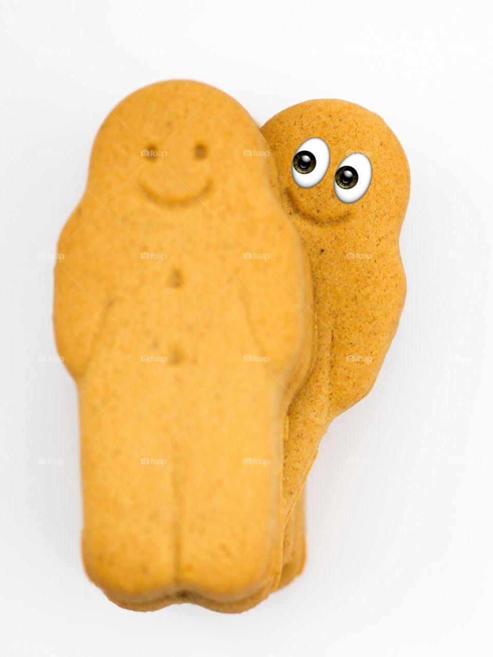 Smiling gingerbread men looking over a shoulder.