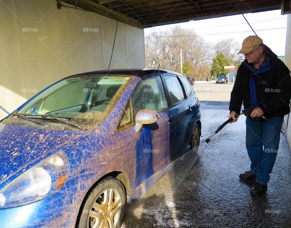 Man washing car using water hose