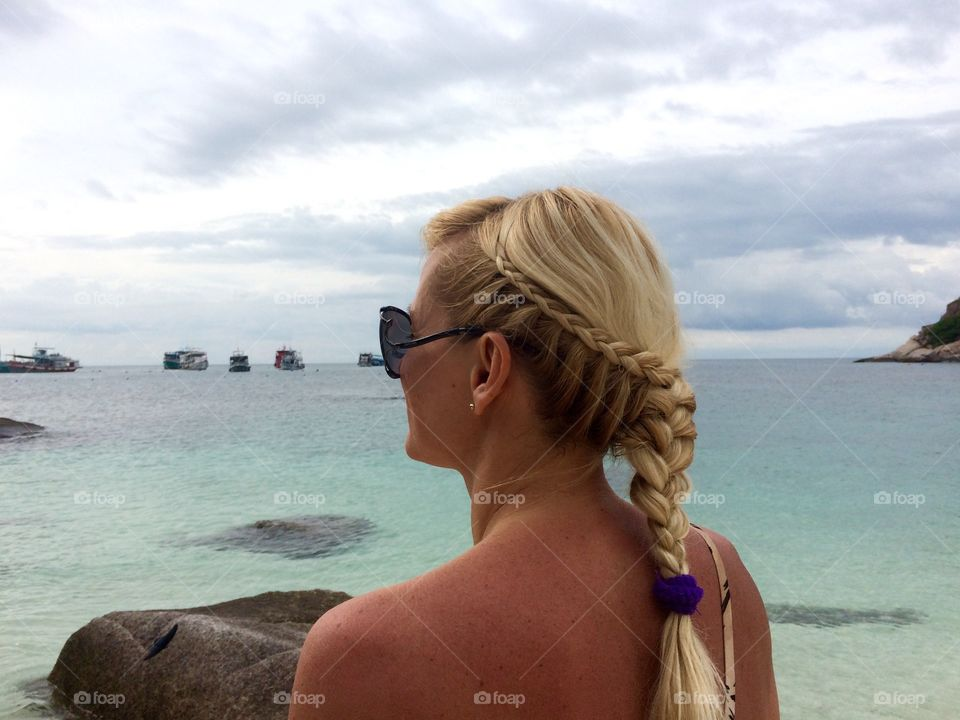 Blonde woman looking at boat in sea