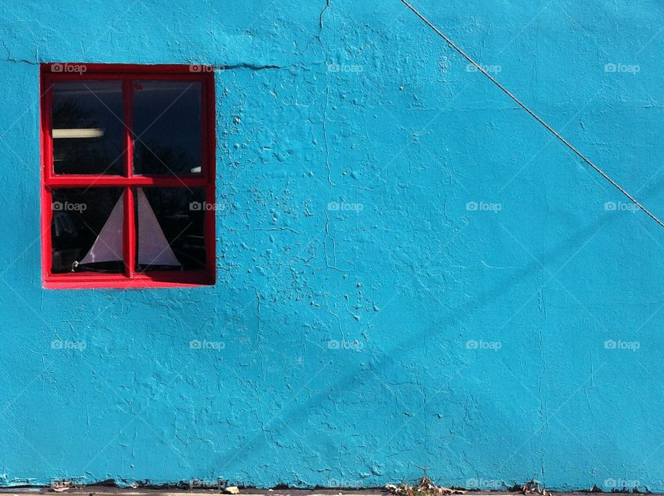 Blue Wall Red Window. A blue wall with a red window.