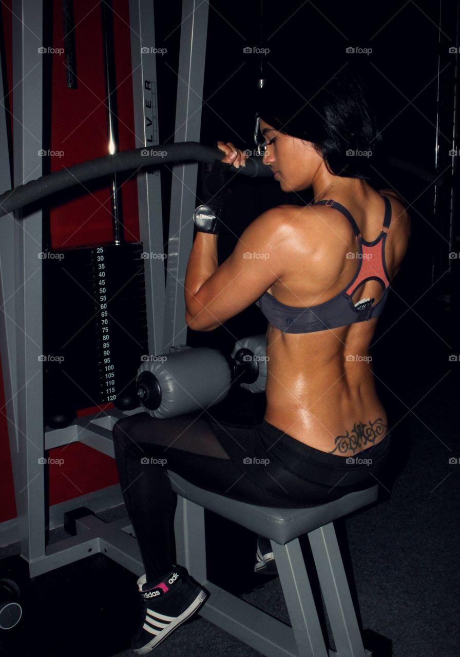 Lat pull down. Sweat. Hard work. Gym.