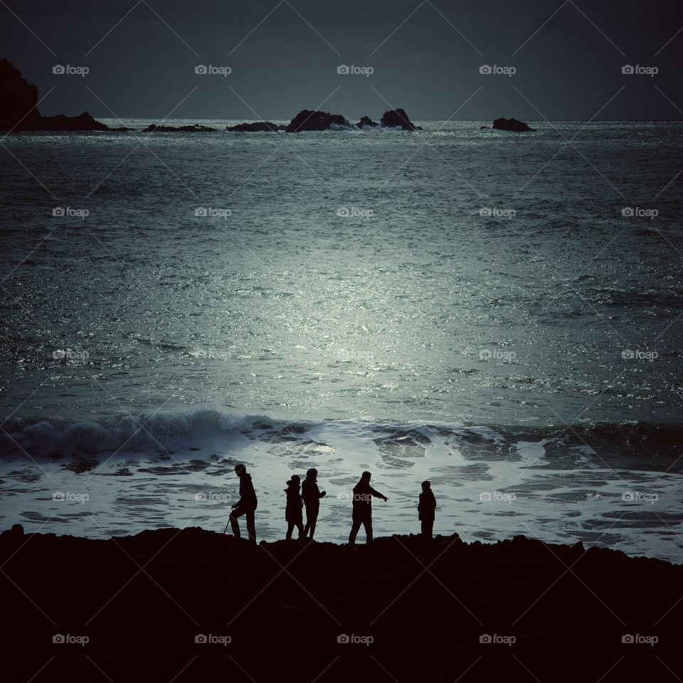 Coastal Moonlit Silhouette. A family of five silhouettes against a moonlit Ocean whilst standing on the shoreline rocks.