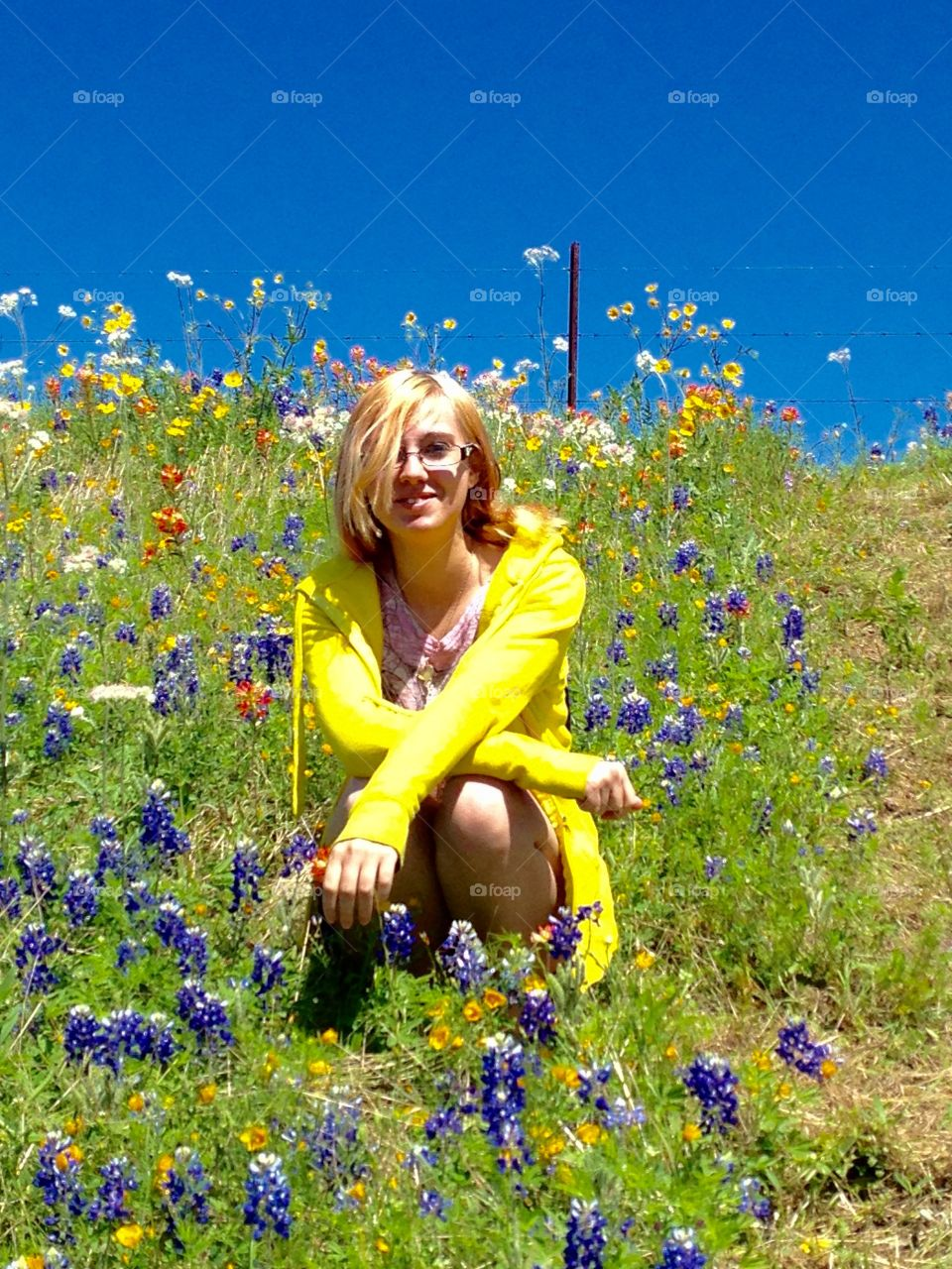 Blonde woman in spectacle sitting on flowers field
