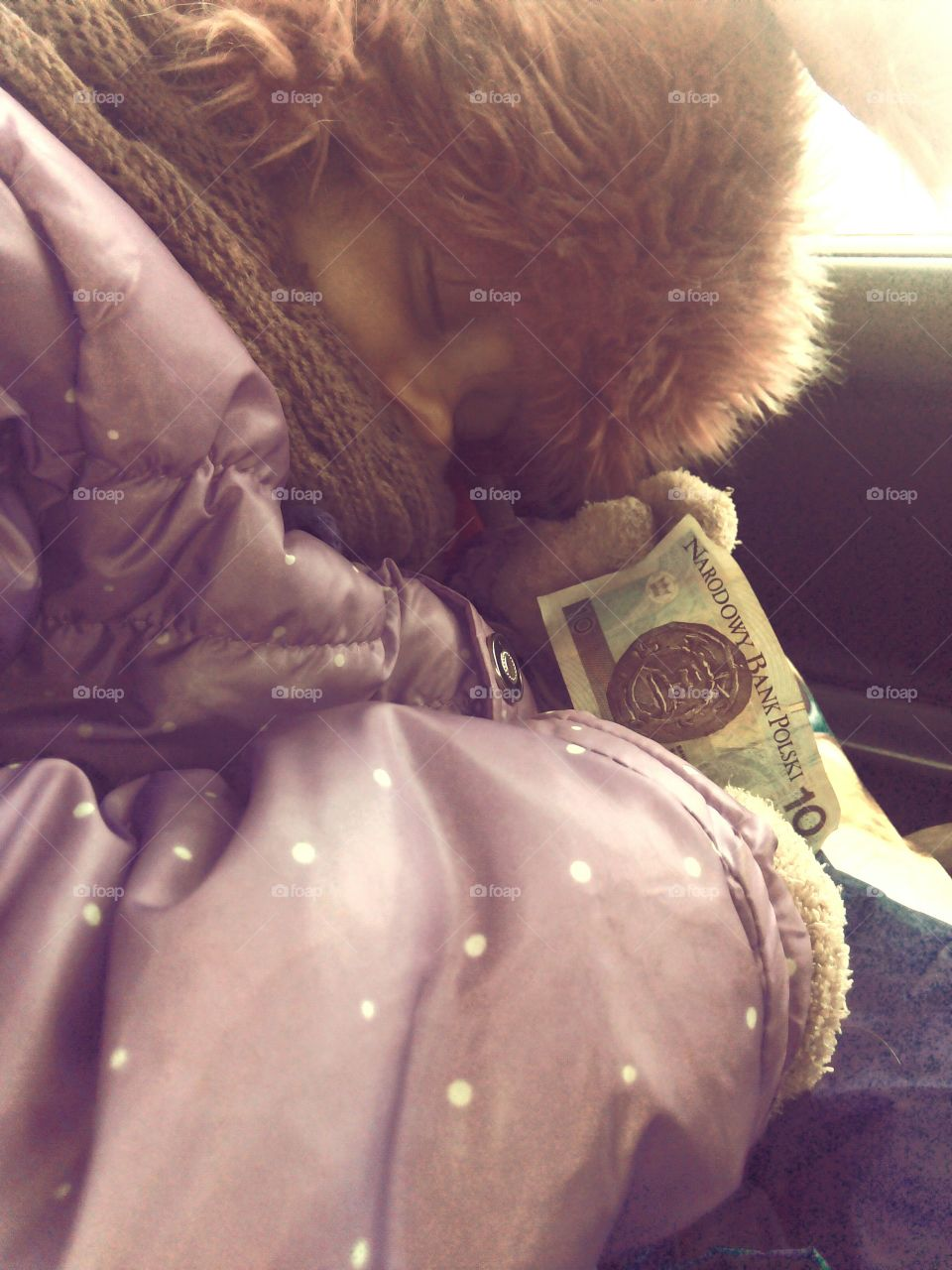 Child holding currency in hand while sleeping