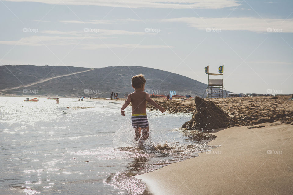 A boy is playing on a beach