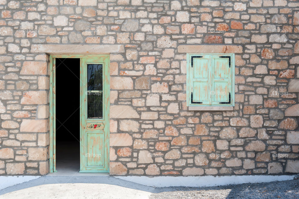 Facade of an old masonry house with green half opened door and closed square window.
