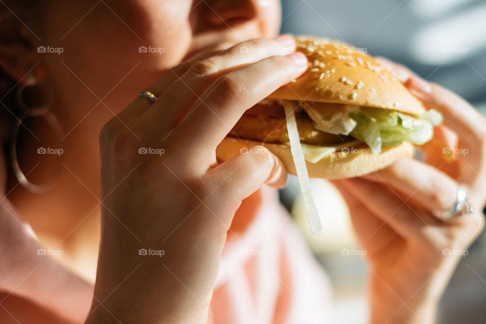 Woman eating fresh burger