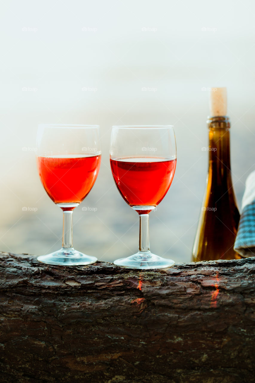 Two wine glasses with red wine standing on tree trunk, on beach, beside wicker basket with bottle of wine