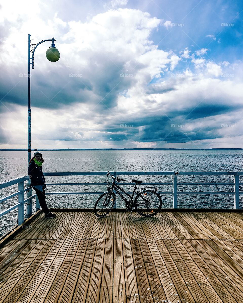 Woman in warm clothing on wooden pier with bicycle