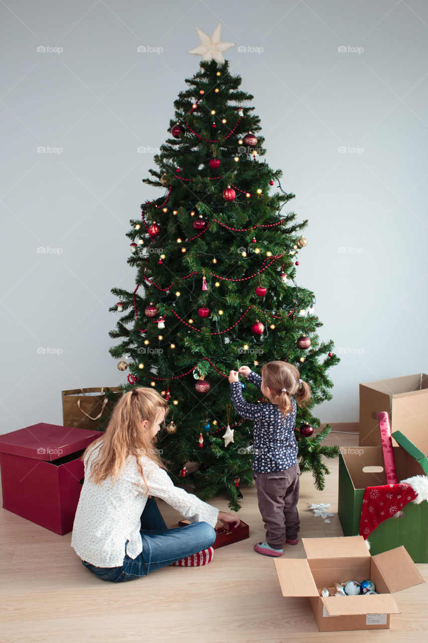 Mother and baby girl decorating christmas tree