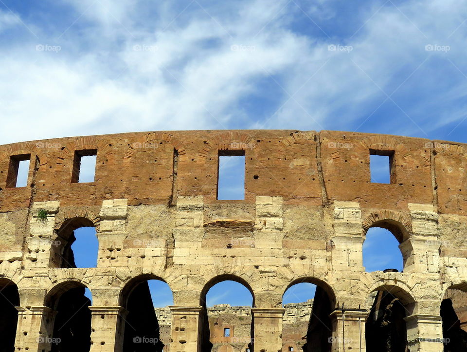 view under the blue sky of the Colosseum walls in rome