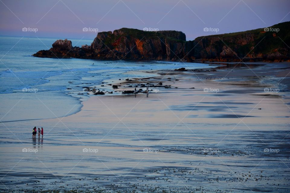 people walking in the seashore during the sunset, rocks andcliffs