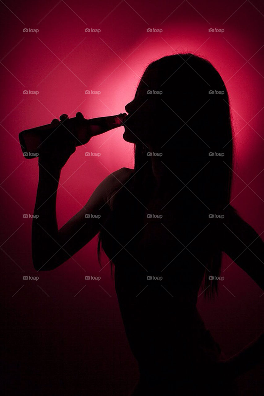 Silhouette. Silhouette of a young girl drinking beer