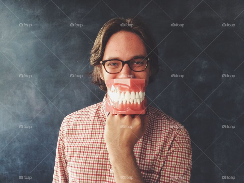 Big teeth. Man with big model of teeth in front of his mouth.