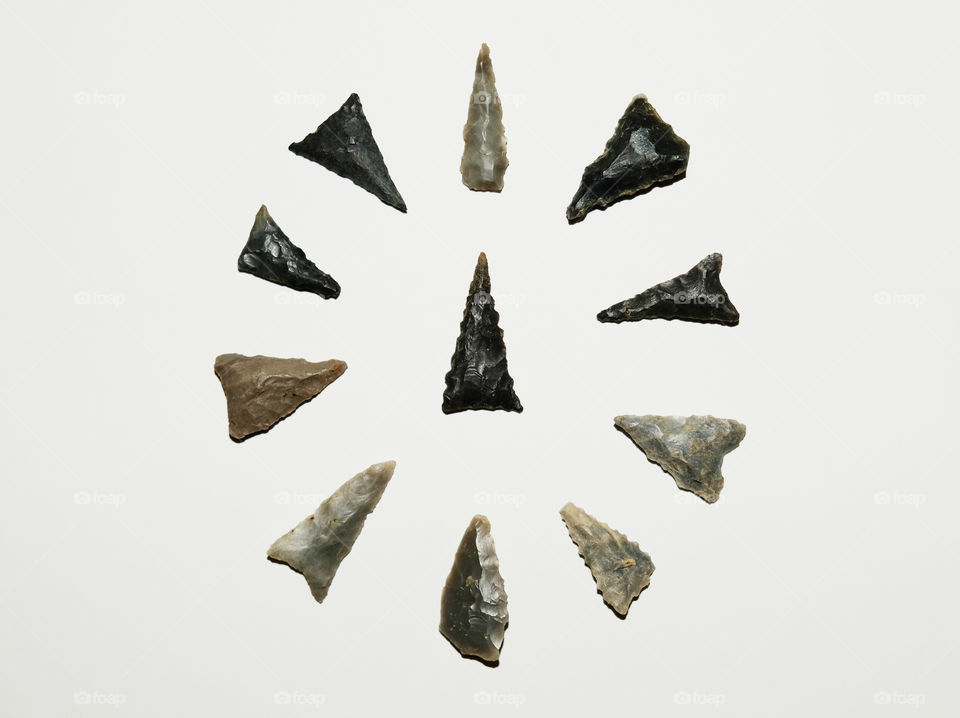 Several arrowheads or bird points arranged in a circular array with a centerpiece on white background. All found in Tennessee.